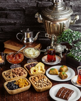 Front view samovar teapot sweets tea set chocolate bar pistachios dried fruits baklava with two glasses of armudu