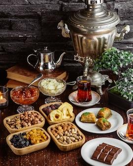 Вид спереди самовар чайник сладости чайный набор шоколадная плитка фисташки сухофрукты пахлава с двумя стаканами армуду