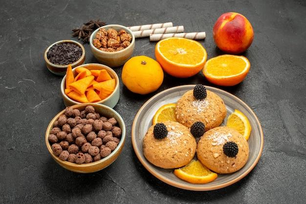 濃い灰色の背景にオレンジスライスと正面図の砂のクッキー甘いフルーツビスケットクッキーティーケーキ