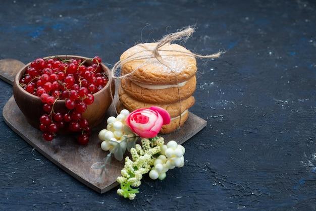 Сэндвич-печенье с кремовой начинкой и свежей красной клюквой на темной поверхности, вид спереди, печенье, сахар, сладкие сливки, фрукты