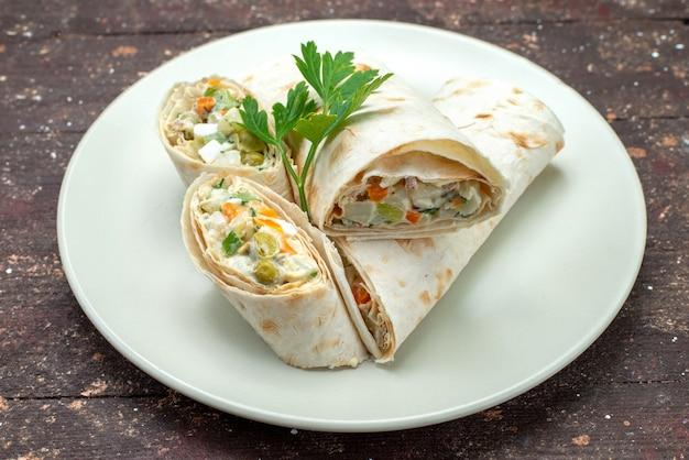 Panino di vista frontale rotola affettato con insalata e carne all'interno del piatto bianco su colore marrone