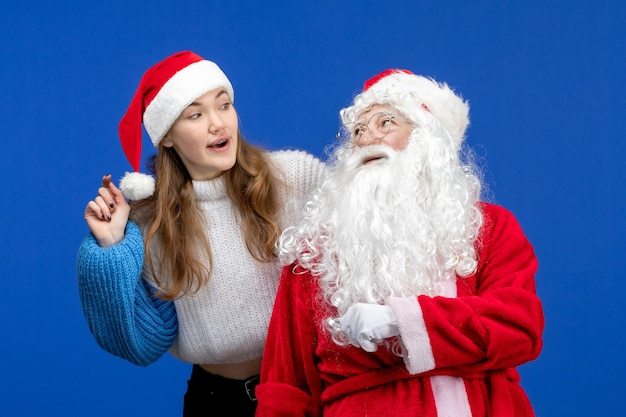 Front view santa claus along with young female on blue christmas color