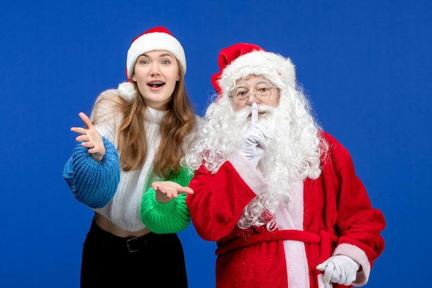 Front view santa claus along with young female on blue holiday christmas color