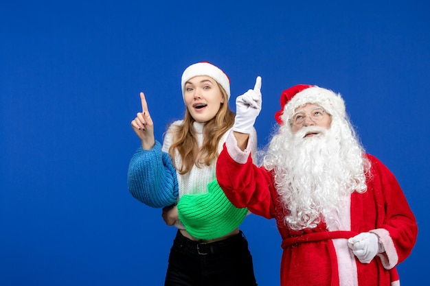 Front view santa claus along with young female pointing at skies on blue new year holiday christmas