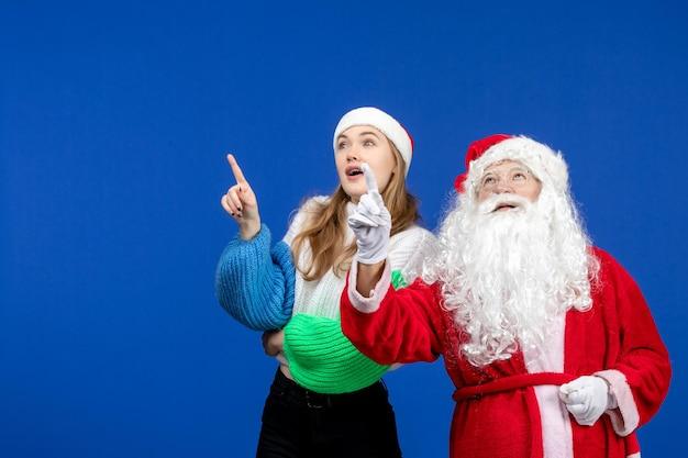 Вид спереди санта-клауса вместе с молодой женщиной, стоящей на синем новогоднем празднике рождественские эмоции фото