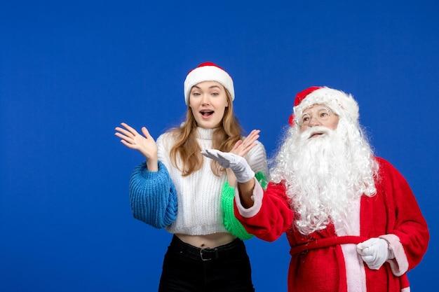 青い新年の休日のクリスマスの感情に立っている若い女性と一緒に正面図のサンタクロース