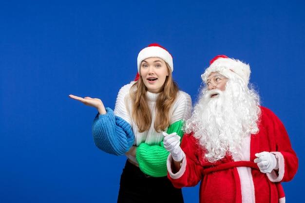 青い新年の休日のクリスマスに立っている若い女性と一緒に正面図のサンタクロース