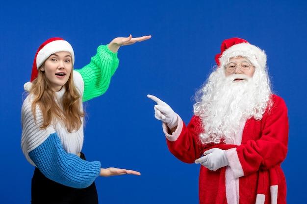 블루에 서 있는 젊은 여성과 함께 전면 보기 산타 클로스