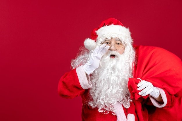 Front view santa claus carrying bag full of presents calling out on red emotion holiday new year christmas