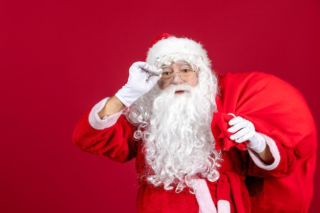 Front view santa claus carrying bag full of presents on red emotion holiday new year christmas