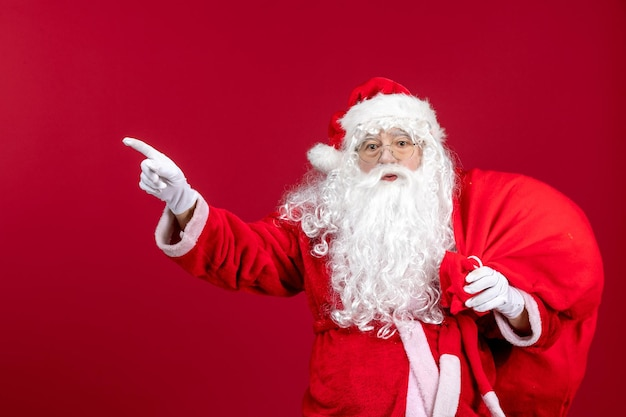 Front view santa claus carrying bag full of presents on red emotion new year christmas holiday male