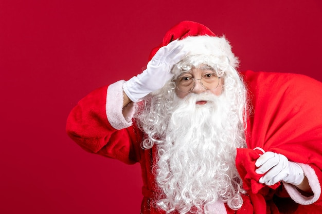 Front view santa claus carrying bag full of presents on red emotion new year christmas holiday