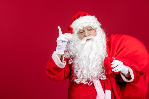 Front view santa claus carrying bag full of presents on the red emotion new year christmas holiday