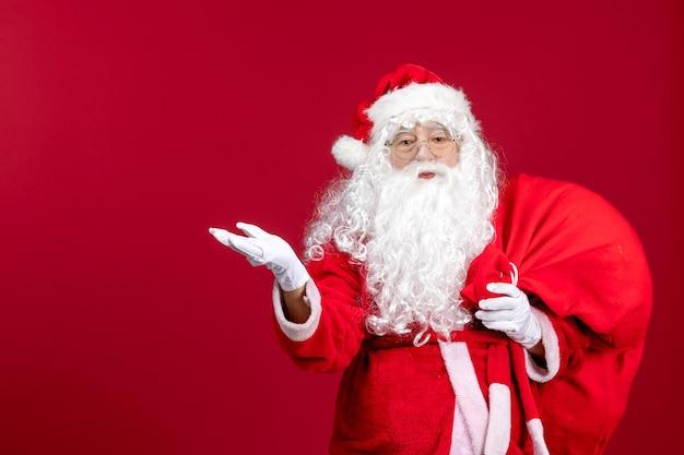 赤いクリスマスの感情の新年の休日にプレゼントでいっぱいの赤いバッグを運ぶ正面のサンタクロース