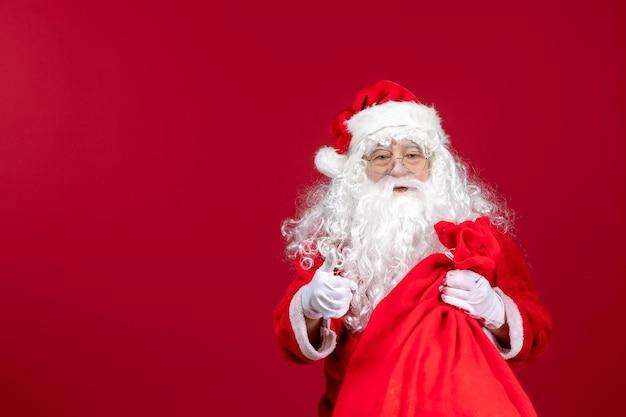 赤いクリスマスの新年の休日の感情のプレゼントでいっぱいの赤いバッグを運ぶ正面のサンタクロース