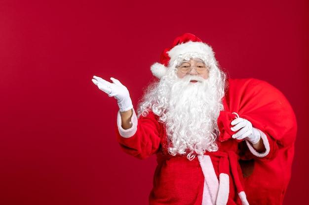 赤い感情の新年のクリスマス休暇にプレゼントでいっぱいの赤いバッグを運ぶ正面のサンタクロース