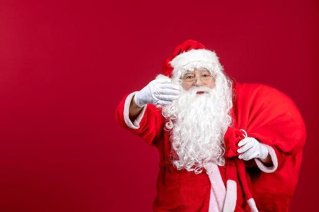 赤い床の感情の新年のクリスマスにプレゼントでいっぱいの赤いバッグを運ぶ正面のサンタクロース