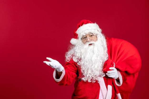 Front view santa claus carrying red bag full of presents on red christmas emotion new year holiday