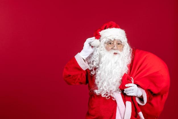 Vista frontale babbo natale che porta una borsa rossa piena di regali durante le vacanze di capodanno con emozione natalizia rossa