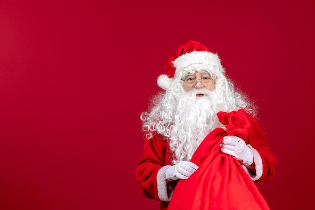 Vista frontale babbo natale che porta una borsa rossa piena di regali sull'emozione delle vacanze di natale capodanno rosso