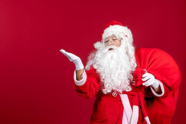 Vista frontale babbo natale che porta una borsa rossa piena di regali durante le vacanze di natale di capodanno di emozione rossa