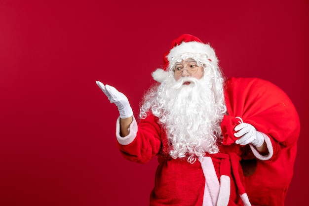 Front view santa claus carrying red bag full of presents on red emotion new year christmas holidays