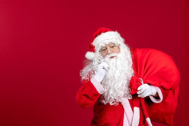 Front view santa claus carrying red bag full of presents on red emotions new year christmas holiday