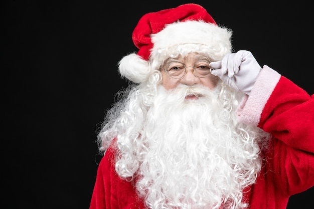 Front view of santa claus in classic red suit with white beard standing on black wall