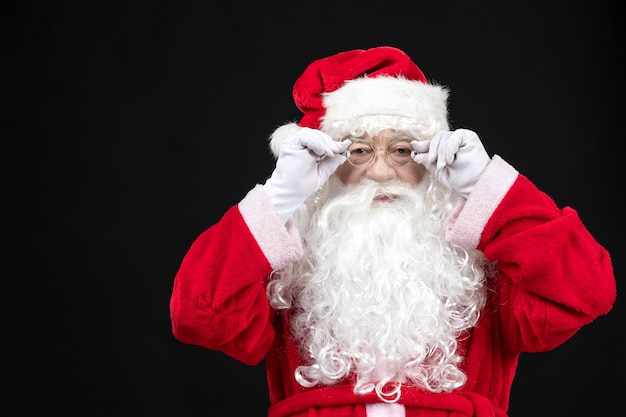 Front view of santa claus in classic red suit with white beard standing on the black wall