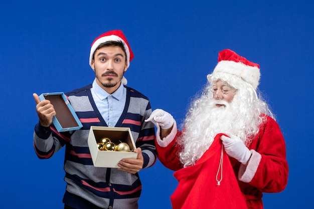 Vista frontale babbo natale che fa un regalo al giovane maschio sulle emozioni del capodanno delle vacanze di natale blu