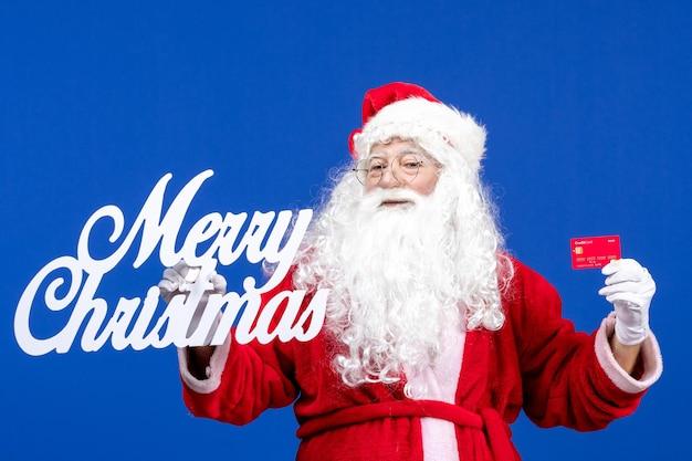 銀行カードと青い色の休日のプレゼントのクリスマスにメリークリスマスの書き込みを保持している正面のサンタクロース