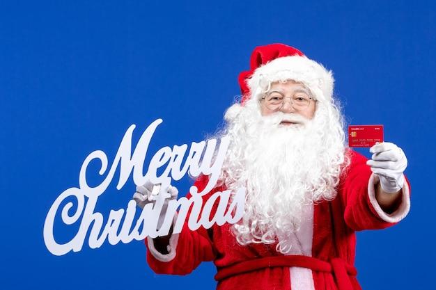 銀行カードと青い色の休日のプレゼントクリスマスにメリークリスマスの書き込みを保持している正面のサンタクロース