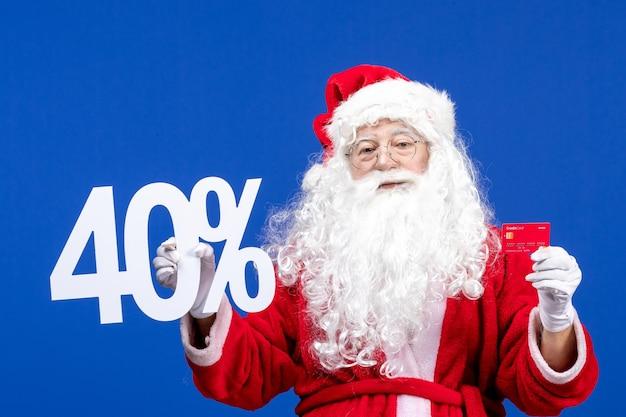 銀行カードを保持し、青い色の休日のプレゼントのクリスマスに書く正面図のサンタクロース