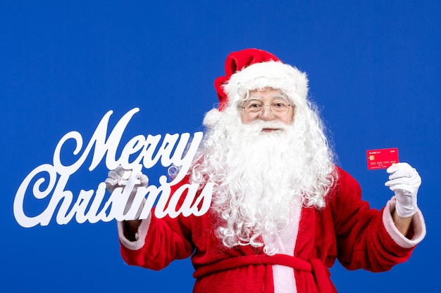 Front view santa claus holding bank card and merry christmas writing on blue color holiday presents xmas