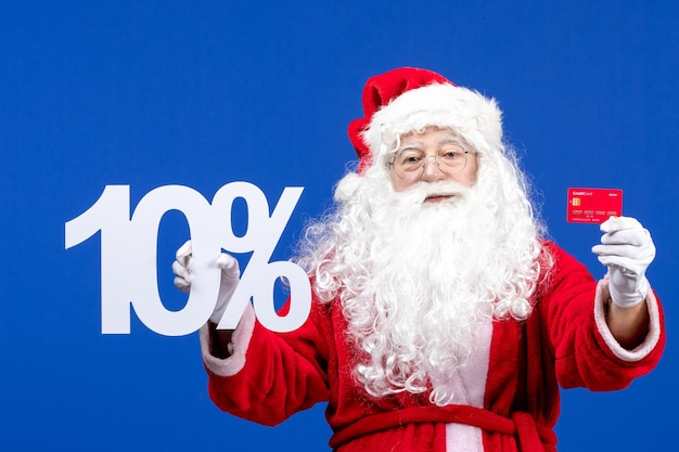 Front view santa claus holding bank card and writing on blue color holiday present xmas