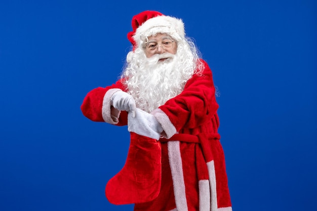 Front view santa claus holding big christmas sock on blue christmas color snow