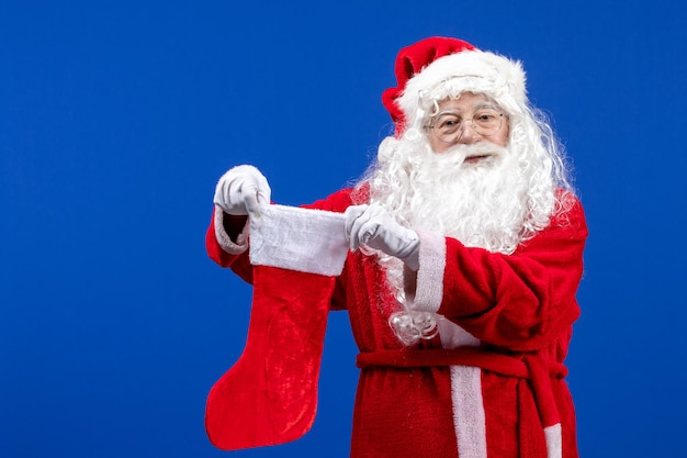 Front view santa claus holding big christmas sock on a blue color christmas snow