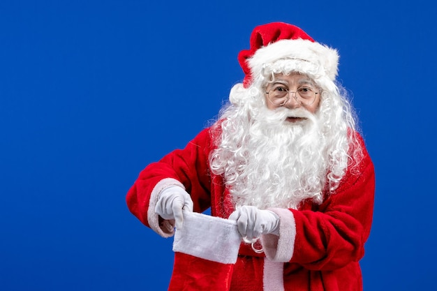 Front view santa claus holding big christmas sock on blue color christmas snow