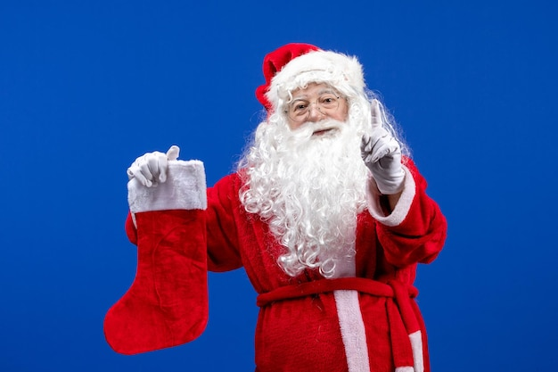Front view santa claus holding big christmas sock on the blue color christmas snow