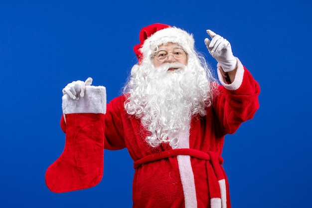 Front view santa claus holding big christmas sock on blue floor color christmas snow