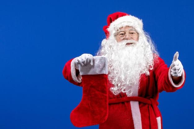 青い色のクリスマスの雪に大きなクリスマスの靴下を保持している正面のサンタクロース