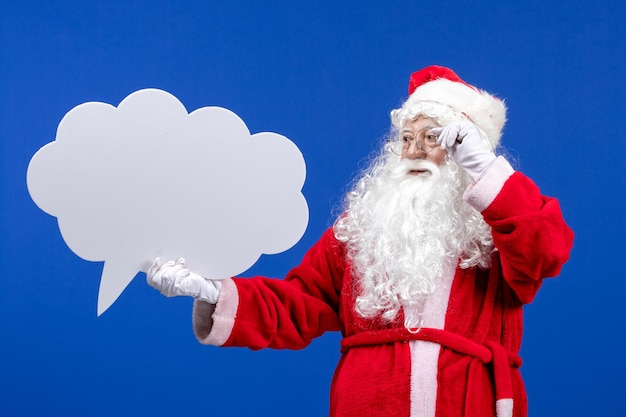 Front view santa claus holding big cloud shaped sign on blue color snow holiday christmas