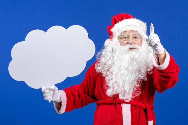 Front view santa claus holding big cloud shaped sign on blue desk snow color christmas