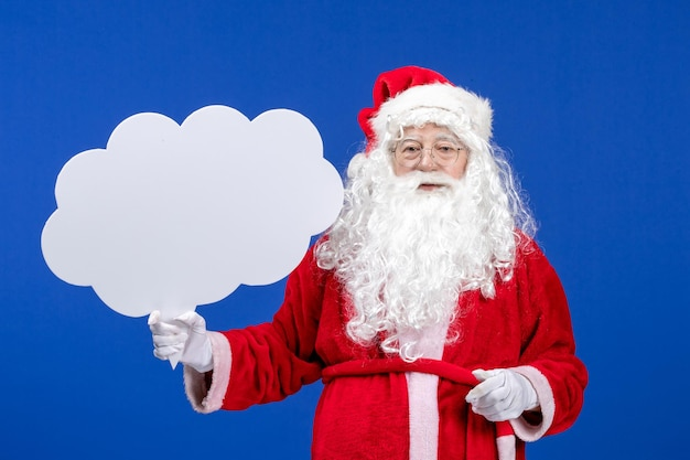 Front view santa claus holding big cloud shaped sign on blue snow christmas color
