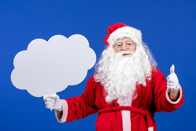Front view santa claus holding big cloud shaped sign on blue snow color christmas holidays