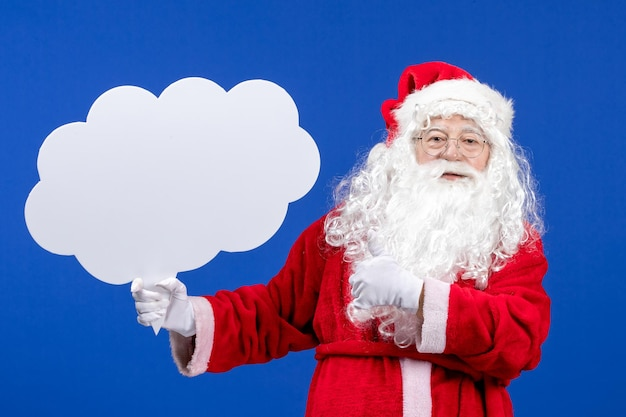 Front view santa claus holding big cloud shaped sign on blue snow color christmas