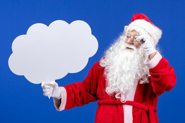 青い雪色のクリスマスに大きな雲の形をした看板を保持している正面のサンタクロース