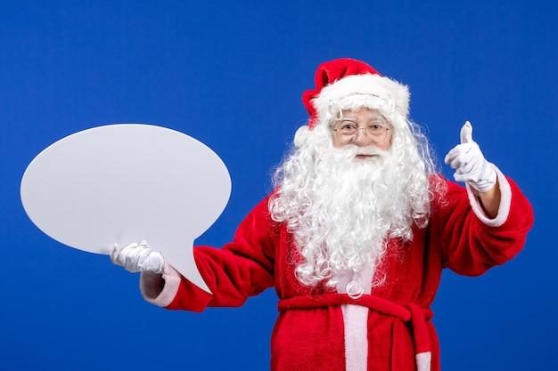 전면 보기 산타 클로스는 파란색 책상 색상 눈 휴가 크리스마스에 큰 흰색 기호를 들고