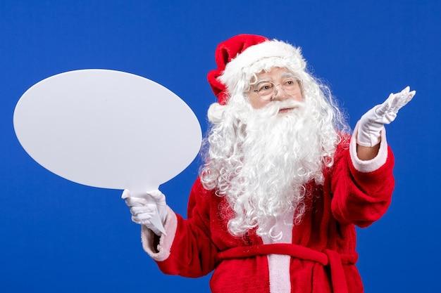 青い雪の休日の色のクリスマスに大きな白い看板を保持している正面のサンタクロース