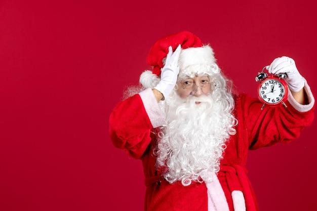 赤いクリスマスの休日の新年の感情の時間に時計を保持している正面図サンタクロース